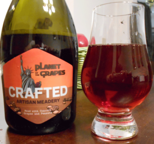 Planet of the Grapes Mead in glass next to bottle